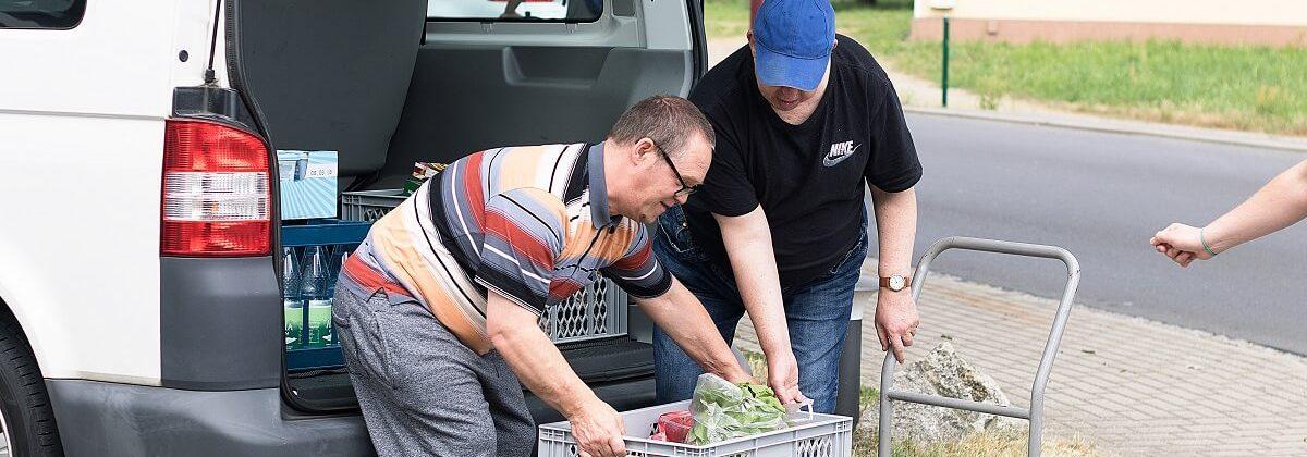 Bewohner helfen dabei, den Einkauf abzuladen