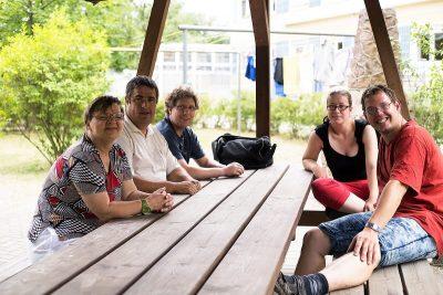 Bewohner sitzen an einem Tisch und reden miteinander