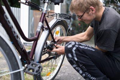 Ein Bewohner schraubt an seinem Fahrrad rum